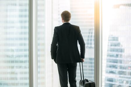 Young businessman with suitcase standing looking at the full length window, before a trip undertaken for work or business purposes, leader with high business aspirations. Rear view