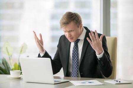 Jonge beklemtoonde knappe zakenman werken bij bureau in moderne kantoor schreeuwen naar laptop scherm en boos over de financiële situatie, jaloers op rivaliserende mogelijkheden, niet in staat om de behoeften van klanten te voldoen