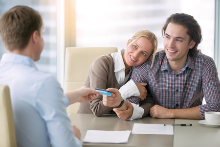 agency agreement: Young happy couple getting a loan concept, first time home buyers, tenancy agreement, agency as a broker between the landlord and tenant, signed all paper and paying with credit card Stock Photo