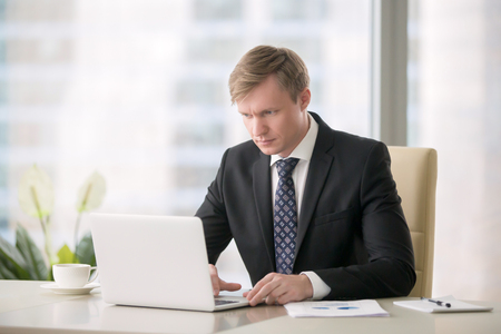 contacting: Young handsome businessman working with laptop at the desk in the modern office, identifying trendsetter ideas by researching industry, publications, tracking delivery, contacting potential partners Stock Photo