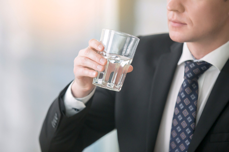 the throughout: Close up of a businessman hand holding a glass with pure water, dehydration, drink enough liquids throughout the day, feeling thirsty, experiencing a headache Stock Photo