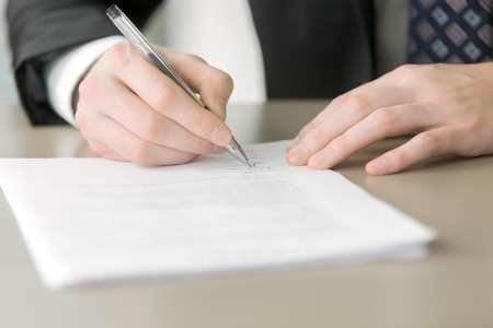 declaring: Close up of male hand putting signature in the contract, entering into the new contract, written statement declaring the price. Business partnership concept Stock Photo