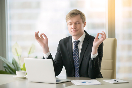 workplace wellness: Young calm businessman working with laptop in yoga pose at modern office desk, minimize day discomfort, focusing on work, boost of energy after important task, keep feeling focused before meeting Stock Photo