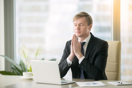 Young businessman working at desk in yoga pose, praying, meditating, relaxing. Stress free work, time for practice, mindfulness and wellbeing, stay healthy on physical, mental emotional level concept Imagens