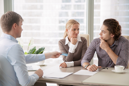 Bank consultant trying to convince clients to get a loan, offering credit card with high interest rate. Middle-class family sorting out finances and budget, not sure in the choice, looking doubtful