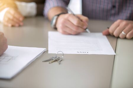 Close up of young people got access to home ownership signing a bank loaning, mortgage program, bound with a loan, buying a home as a good option, couple meeting with bank worker or real estate agent Stock Photo