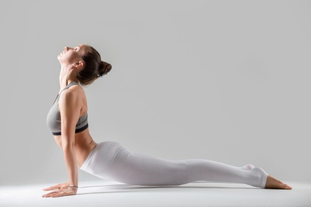 Young attractive woman practicing yoga, standing in upward facing dog exercise, Urdhva mukha shvanasana pose, working out wearing sportswear, indoor full length, isolated, grey studio background