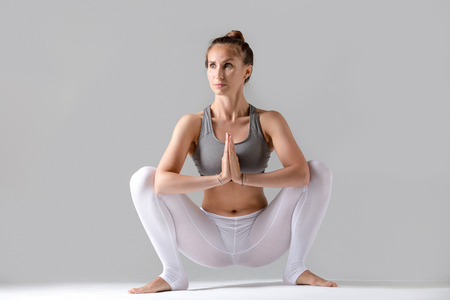 Young attractive woman practicing yoga, sitting in Garland exercise, Malasana pose, working out wearing sportswear, white pants, gray top, indoor full length, isolated against grey studio background Stock Photo