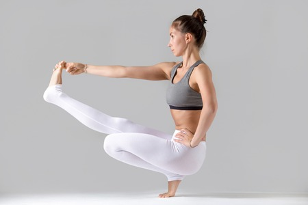 hasta: Young attractive woman practicing yoga, doing Toe Balance, variation of Extended Hand to Big Toe pose with squat, working out wearing sportswear, indoor full length, isolated, grey studio background