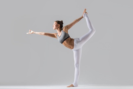 Young attractive woman practicing yoga, standing in Lord of the Dance exercise, Natarajasana pose, working out wearing sportswear, white pants, gray top, indoor full length, grey studio background Фото со стока - 70006568