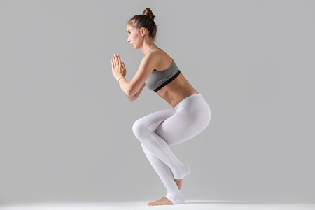 Young attractive woman practicing yoga, standing in Eagle exercise, Garudasana pose, working out wearing sportswear, white pants, gray top, indoor full length, isolated against grey studio background Stock Photo