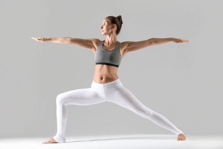 Jonge aantrekkelijke vrouw het praktizeren yoga, die zich in Strijder bevinden Twee oefening, Virabhadrasana II stelt, het uitwerken van het dragen van sportkleding, binnen volledige lengte, geïsoleerde, grijze studioachtergrond Stockfoto