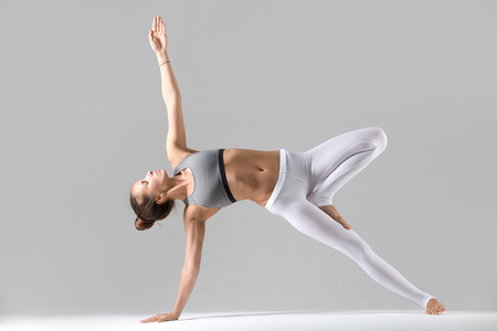 Young attractive woman practicing yoga, stretching in Side Plank exercise, Vasisthasana pose, working out wearing sportswear, white pants, indoor full length, isolated against grey studio background