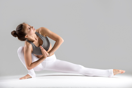 Young woman practicing yoga, stretching in Revolved Head to Knee Forward Bend exercise, Baddha Ardha Samakonasan pose, working out wearing sportswear, indoor full length, grey studio background