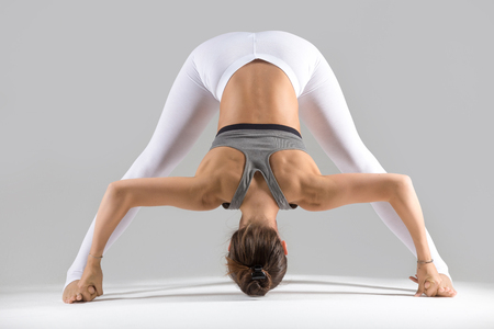 Young attractive woman practicing yoga, standing in Wide Legged Forward Bend exercise, Prasarita Padottanasana pose, working out wearing sportswear, indoor full length, grey studio background Stock Photo