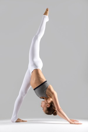 Young woman practicing yoga, stretching in one legged downward facing dog exercise, eka pada adho mukha svanasana pose, working out wearing sportswear, indoor full length, grey studio background