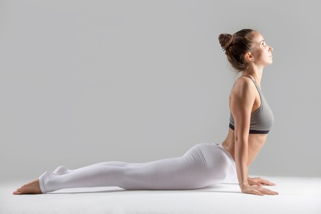 Young attractive woman practicing yoga, stretching in Cobra exercise, Bhujangasana pose, working out wearing sportswear, indoor full length, isolated against grey studio background