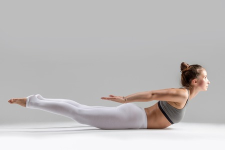 Young attractive woman practicing yoga, stretching in Double Leg Kicks exercise, Salabhasana pose, working out wearing sportswear, white pants, indoor full length, isolated, grey studio background
