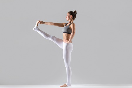 hasta: Young attractive woman practicing yoga, standing in Extended Hand to Big Toe exercise, Utthita Hasta Padangustasana pose, working out wearing sportswear, indoor full length, grey studio, profile Stock Photo