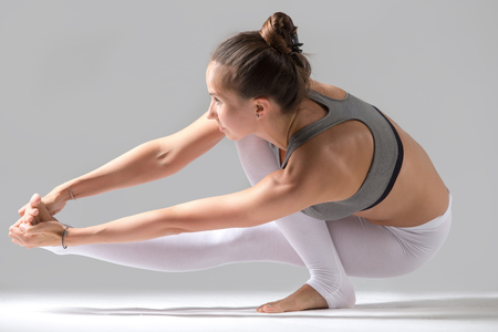 Young attractive model girl practicing yoga, doing Squat Balance with twisting variation of Extended Hand to Big Toe pose, working out indoors, full length, isolated, grey studio background Stock Photo