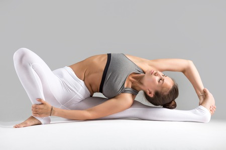 janu: Young woman practicing yoga, stretching in Revolved Head to Knee Forward Bend exercise, Parivrtta Janu Sirsasana pose, working out wearing sportswear, indoor full length, grey studio background