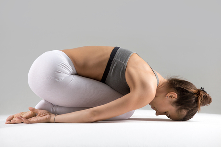 Young attractive woman practicing yoga, sitting in Child exercise, Balasana pose, working out wearing sportswear, white pants, bra, indoor full length, isolated against grey studio background Stock Photo