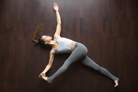 Beautiful young model working out at home, doing yoga exercise on floor, lying in Parivrtta Supta Padangushthasana, reclined variation of Twisting Extended Hand to Big Toe pose. Top view. Full length
