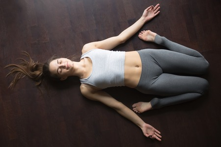 Beautiful young woman working out at home, doing yoga exercise on wooden floor, lying in Reclining Hero pose, Supta Virasana posture, resting after practice. Full length, top view Stok Fotoğraf - 69024477