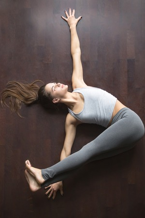 revolved: Beautiful young model working out at home, doing yoga exercise on floor, lying in reclining Belly Twist Pose, variation of Jathara Parivartanasana, practice for abs and core. Top view. Full length