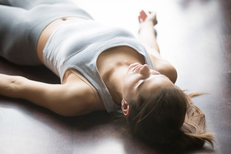 Attractive young woman working out at home, doing yoga exercise on the floor, lying in Shavasana Corpse or Dead Body Posture , resting after practice, meditating, breathing. Close-up