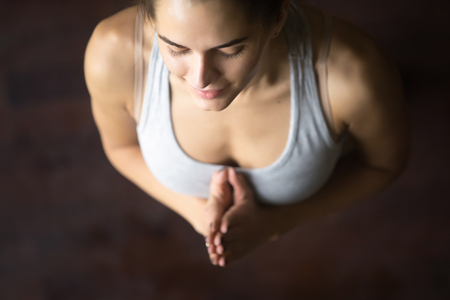 Close up portrait of beautiful young happy model girl working out at home, doing yoga exercise, standing in mountain, Tadasana pose with Namaste and closed eyes, meditating, praying. High angle view Stock Photo