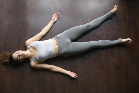 전망: Beautiful young woman working out at home, doing yoga exercise on wooden floor, lying in Shavasana Corpse or Dead Body Posture , resting after practice, meditating, breathing. Full length, top view