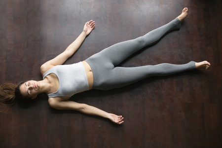 Beautiful young woman working out at home, doing yoga exercise on wooden floor, lying in Shavasana Corpse or Dead Body Posture , resting after practice, meditating, breathing. Full length, top view