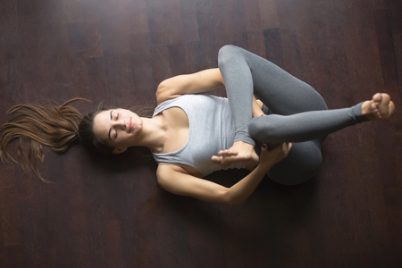 Beautiful young model working out at home, doing yoga exercise on floor, lying in Eye of the Needle hip stretch pose Dead or Reclining Pigeon posture , resting after practice. Full length, top view Stockfoto