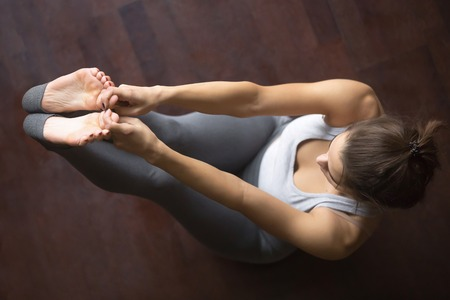 Beautiful young model working out at home, doing yoga exercise on floor, siting in Both Big Toe Pose, Paripurna Navasana, Padangustasana posture. Core training. Top view. Full length Imagens