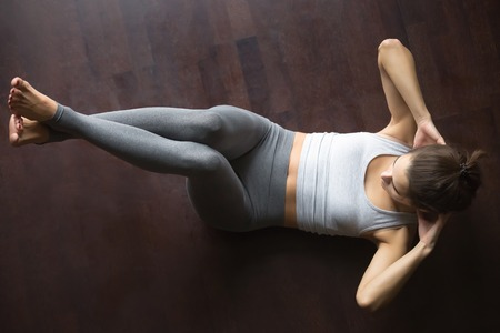 upper floor: Beautiful young model working out at home, doing fitness exercise on floor, Abdominal Knee Crunches for upper and lower abs, Sit Ups with hands behind the neck. Core training. Top view. Full length