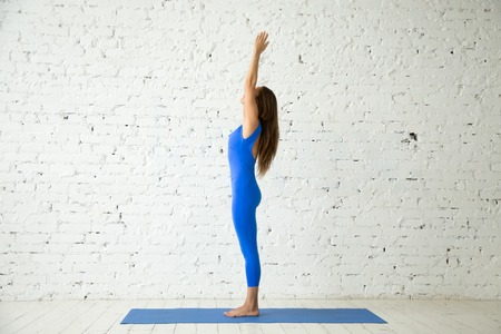 Young attractive woman practicing yoga, standing in mountain exercise, Tadasana pose, working out, wearing sportswear, blue jumpsuit, indoor full length, white loft studio background. Side view