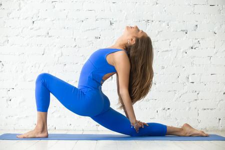 Jonge aantrekkelijke vrouw beoefenen van yoga, die zich in ruiter van het paard oefening, anjaneyasana pose, het uitwerken, het dragen van sportkleding, blauwe jumpsuit, binnen volledige lengte, witte loft studio achtergrond Stockfoto