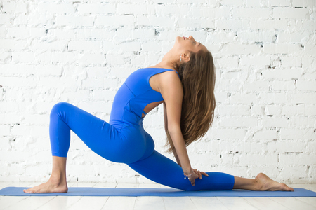 Young attractive woman practicing yoga, standing in Horse rider exercise, anjaneyasana pose, working out, wearing sportswear, blue jumpsuit, indoor full length, white loft studio background 版權商用圖片 - 70070550