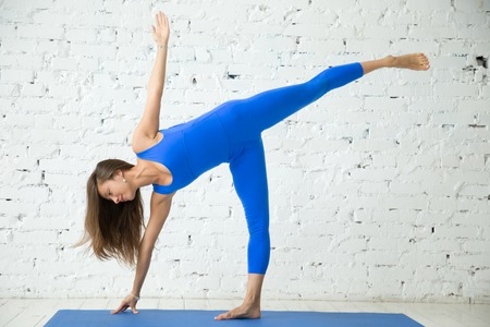 chandrasana: Young attractive smiling woman practicing yoga, standing in Half Moon exercise, Ardha Chandrasana pose, working out, wearing sportswear, blue suit, indoor full length, white loft studio background