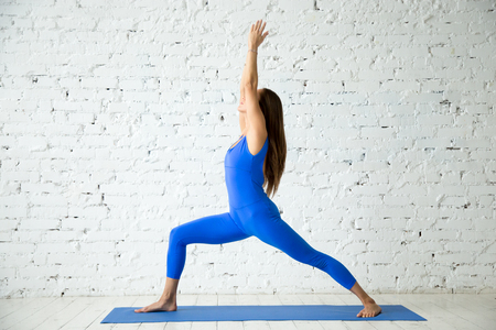 Young attractive woman practicing yoga, standing in Virabhadrasana 1 exercise, Warrior one pose, working out, wearing sportswear, blue suit, indoor full length, white loft studio background Imagens