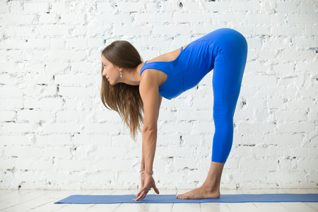 ashtanga: Young attractive woman practicing yoga, head to knees, Standing Half forward bend exercise, Ardha uttanasana pose, working out, wearing sportswear, blue suit, full length, white studio background