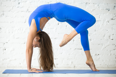 eka: Woman practicing yoga, standing in One legged Wheel exercise, Bridge pose, working out, wearing sportswear blue suit, indoor full length, white loft studio background. Tattoo on foot Way of heart