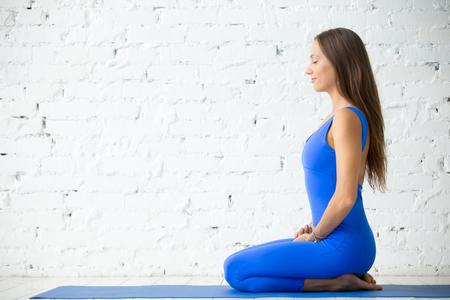 Young attractive woman practicing yoga, sitting in seiza pose, vajrasana exercise, working out, wearing sportswear, blue suit, indoor full length, white loft studio background, copy space, profile