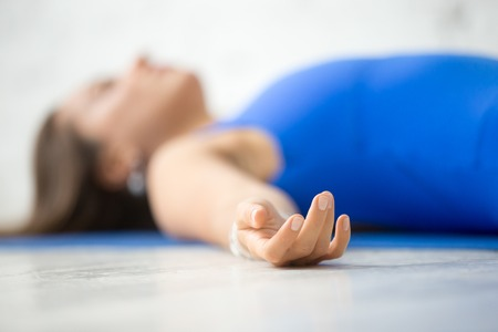 Young attractive woman practicing yoga, lying in Dead Body, Corpse exercise, Savasana pose, working out wearing sportswear, blue suit, indoor, white studio background, focus on the hand