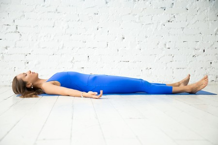 Young attractive woman practicing yoga, lying in Dead Body, Corpse exercise, Savasana pose, working out wearing sportswear, blue suit, indoor full length, white loft studio background. Copy space