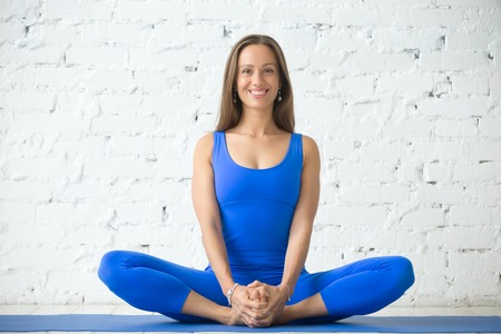 Young attractive woman practicing yoga, sitting in Butterfly exercise, baddha konasana pose, working out, wearing sportswear, blue suit, indoor full length, white loft studio background Stock Photo