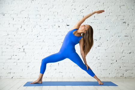 shanti: Young attractive woman practicing yoga, standing in Viparita Virabhadrasana exercise, Reverse Warrior pose, working out, wearing sportswear, blue suit, indoor full length, white loft studio background Stock Photo