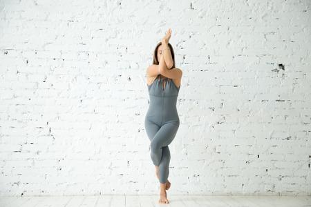 Jonge aantrekkelijke vrouw beoefenen van yoga, staande in Eagle oefening, Garudasana pose, uit te werken, het dragen van sportkleding, grijs pak, indoor volledige lengte, witte studio achtergrond