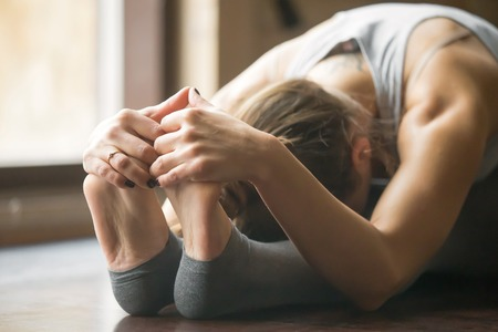 Close up of young woman practicing yoga, sitting in Seated forward bend exercise, paschimottanasana pose, working out, wearing sportswear, grey pants, bra, indoor, home interior background, horizontal Foto de archivo